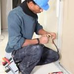 électricien en attachant du ruban adhésif un fil — Photo