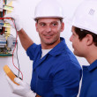 Stock Photo: Electrical safety inspectors verifying central fuse box