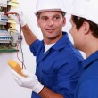 Stock Photo: Two electricians testing fuse box