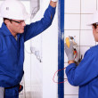 Male electrician supervising female apprentice — Stockfoto