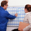 Factory worker showing the schedule to the manager - Stock Photo