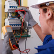Female electrician taking reading from fuse box — Stock Photo #7911814