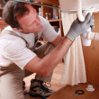 Labourer fixing sink - Stock Photo
