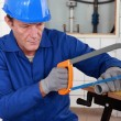 Plumber cutting length of plastic pipe - Stock Photo