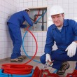 Two plumbers working, one plumber is connecting pipes — Stock Photo #7912325