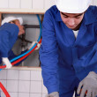 Stock Photo: Plumber measuring and cutting plastic tube