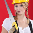Stock Photo: Womwith hardhat and handsaw