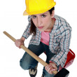 Female builder holding a sledge hammer - Stock Photo