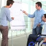 uomo su sedia a rotelle con i colleghi — Foto Stock