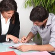 Stock Photo: Businesswomhelping her client fill in paperwork