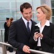 Businessman and businesswoman watching mobile phone outdoors — Stock Photo