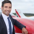 Young businessman standing in front of an airplane — Stock Photo #7914386