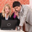 Man on a cellphone and a woman on a laptop - Stock Photo