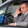 Architect in car using mobile telephone - Stock Photo