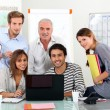 Young team of sitting around a laptop with an older guy - Foto Stock