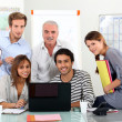 Young team of sitting around a laptop with an older guy - Stock Photo