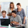Co-workers gathered around computer screen — Stock Photo