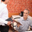 Stock Photo: Waiter proposing menu to client