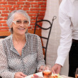 Young waiter serving an older woman in a restaurant — Stock Photo