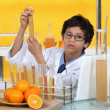 Little boy conducting experiment on orange juice — Stock Photo