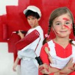 Children painting a wall red - Stock fotografie