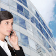 Smart businesswoman making call outdoors near building - Stock Photo