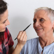 Young woman applying makeup to an elderly lady — Stock Photo #7915207