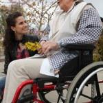 ung kvinna med en äldre dam i en rullstol — Stockfoto