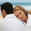 A man and a woman wearing dressing gowns on a beach. — Stock Photo #7915496