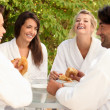 图库照片: Two couples sharing joke over breakfast in garden