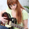 Ginger-haired girl playing guitar - Stock Photo