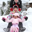 Stock Photo: Family sledging downhill