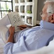 Senior doing crossword in magazine — Stockfoto #7915782