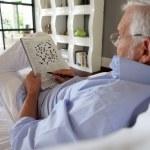 Senior doing a crossword in a magazine — Stock Photo