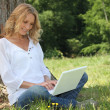 Blond woman sat by tree with laptop computer — Stock Photo