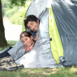 Young couple peeking out of their tent — Stock fotografie
