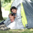 Young couple peeking out of their tent — Stockfoto