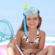 Young girl on the beach with snorkel, mask and fishing net — Stock Photo