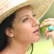 Woman in a straw hat about to bite an apple — Stock Photo