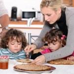 Parents preparing breakfast for children — Stock Photo