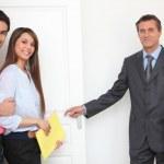 couple montrant-agent immobilier autour de propriété — Photo