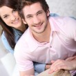 Young couple all smiles with djembe drum - Stock Photo