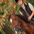 Blond woman riding horse - Stock Photo