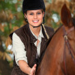 Blonde woman riding a horse — Stock Photo #7917532