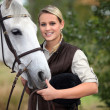 Young woman taking care of her horse — Stock Photo #7917542