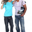 Man with rollerblades and teen carrying skateboard - Foto Stock