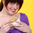 Woman eating a cone of chips — Stock Photo