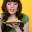 Woman eating plate of pasta — Stock Photo #7918225