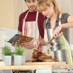 Молодая женщина резки курица в кухне — Стоковое фото