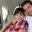 Young couple in the back of a car — Stockfoto